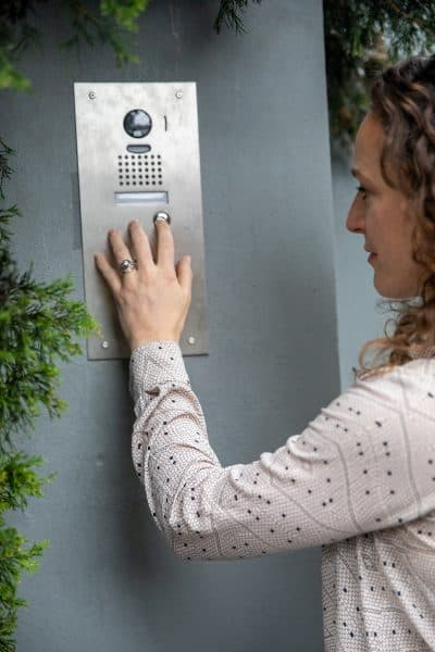 Photograph of a woman in a shirt using a video intercom system to enter a building