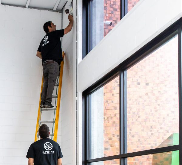 Photograph of two BPoint Security Technicians choosing security cameras for a corner of a commercial building