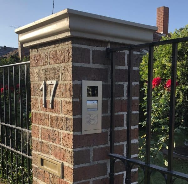 Photograph of a home access control system on a brick structure at a front gate numbered 17