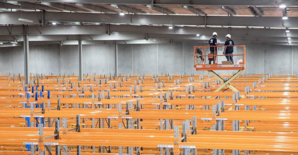 Security technicians installing a warehouse security system using a scissor lift above the aisles of the warehouse