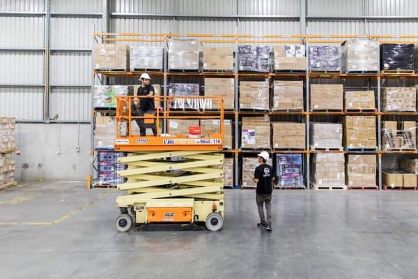 Security technicians working at a Moorabbin warehouse installing a commercial security system using a scissor lift